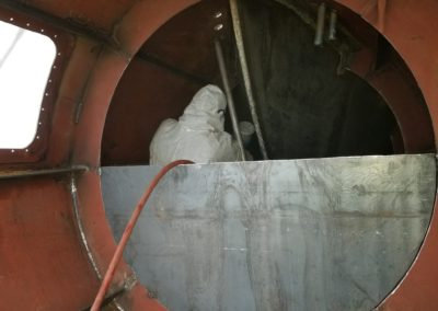 Beginning phase of the bow thruster installation, including fabrication of piping for hydraulic hoses. The technician in the space sprays a coat of Red Oxide Flash Weld Primer in the interior.
