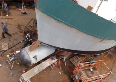 "The bulbous bow dome, now welded in position, was formed at AMS Industries of Vancouver, B.C., specialists in metal spinning [<a href:""http://www.amsind.com""><FONT color=#00bbff>http://www.amsind.com</FONT></a>]. The technician shapes the hull fairing plates at the bow using doorskin templates. The fairing plates serve to push the bow wave up the hull and to stop debris from catching in the intersection where the hull meets the bulb/dome. This helps to make <u>Stormie B</u>'s motion smoother in building seas."
