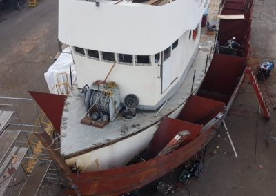 Port side hull sheeting/plating formed over the erected partition bulkheads. The new stem section was cut from 12-inch schedule 80 mild steel pipe.