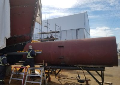 Measuring against the vessel hull to mark for the first cuts in the bow hull, which is achieved by measuring the distance forward from all points on the vessel hull to the bow hull, using a 10' level straight-edge.