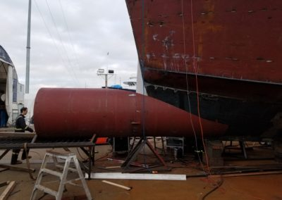 The excess steel has been cut away, and the bulbous bow is being slid back into position against hull for final fitting.