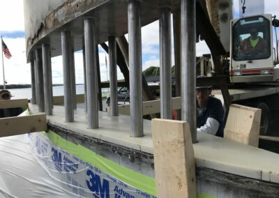 With the G10 in place, the crane is used to carefully set the keel onto the keel bulb.